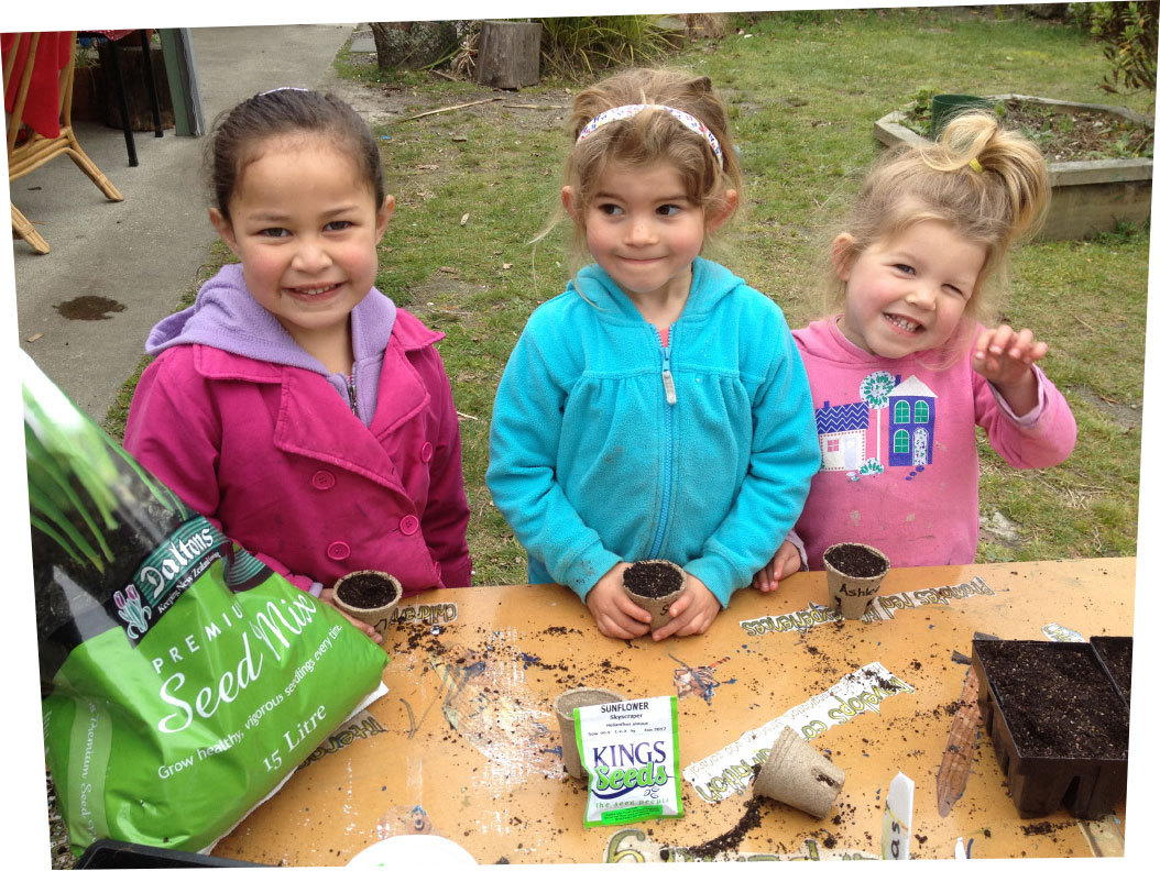 Three smiling girls with pots containingtheir newly planted sunflowers